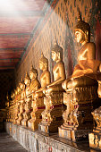 Close up shiny golden buddha statues in a row with beam of light in buddhist temple in Bangkok, Thailand