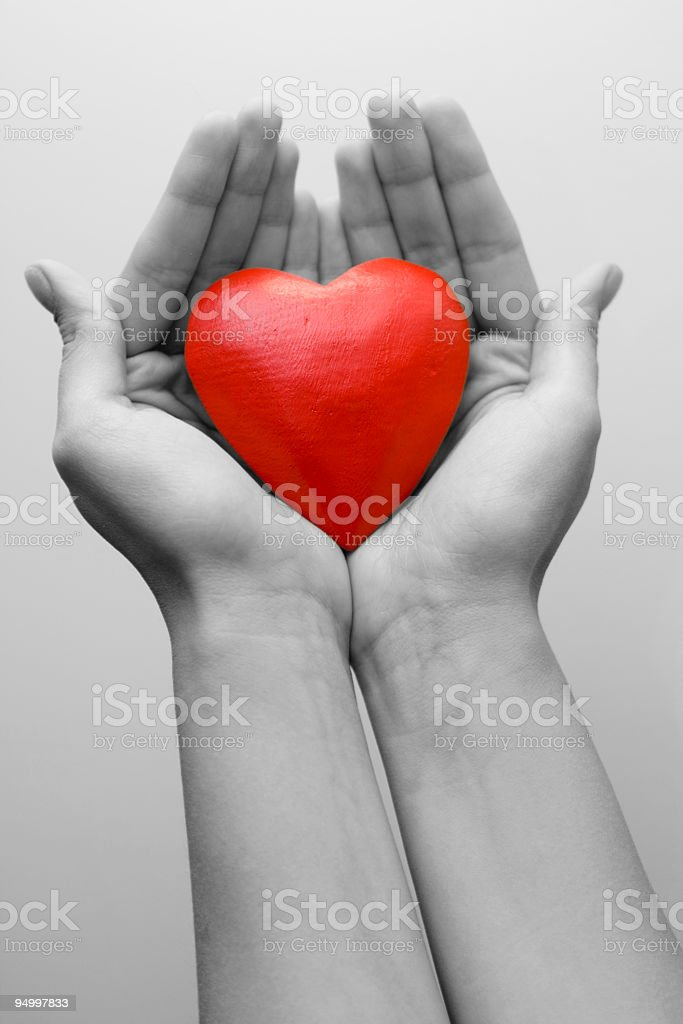 A shiny heart in a females palms royalty-free stock photo