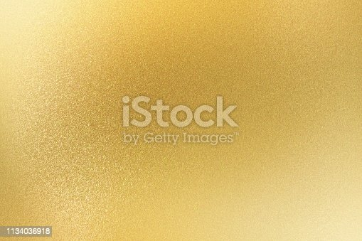 Shiny light gold metallic sheet, abstract texture background