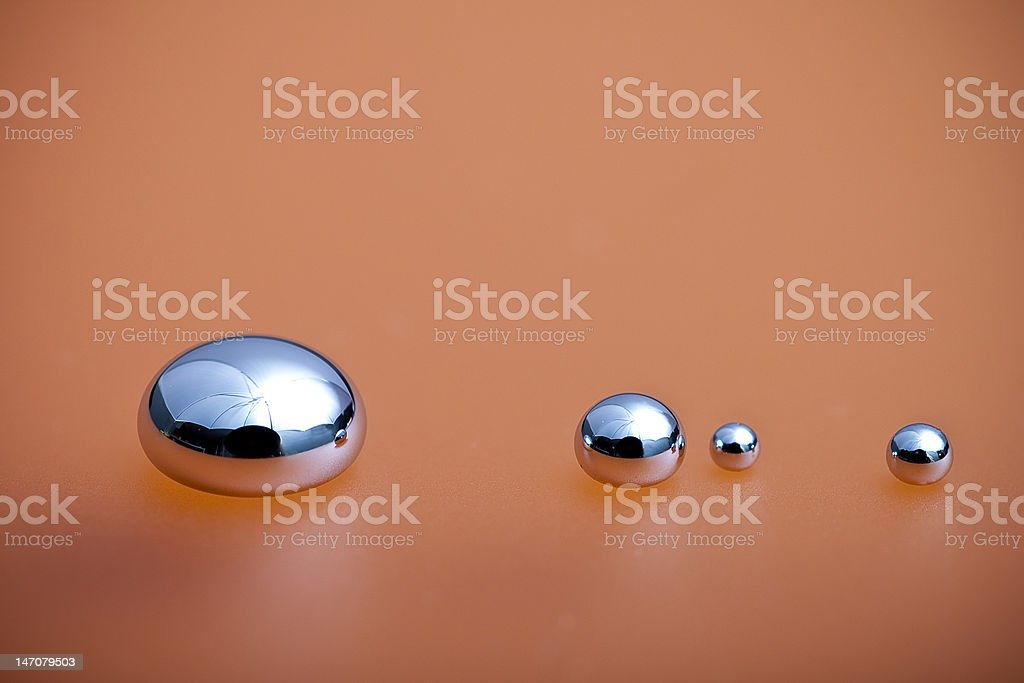 Shiny Mercury Shiny Mercury drops on a orange background Chrome Stock Photo