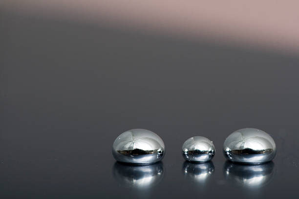 Shiny Mercury Shiny Mercury drops on a grey background mercury metal stock pictures, royalty-free photos & images