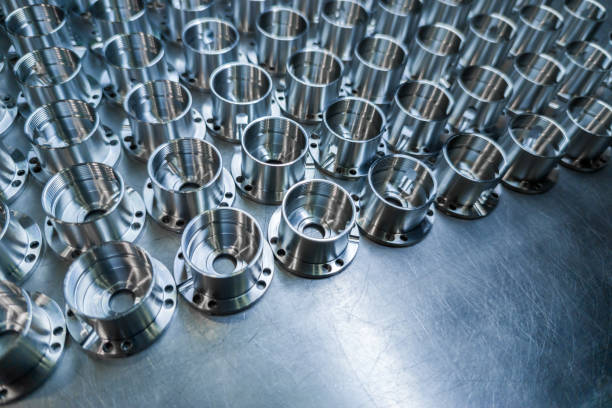 Shiny metal aerospace parts after cnc machining on steel surface with selective focus, industrial background stock photo