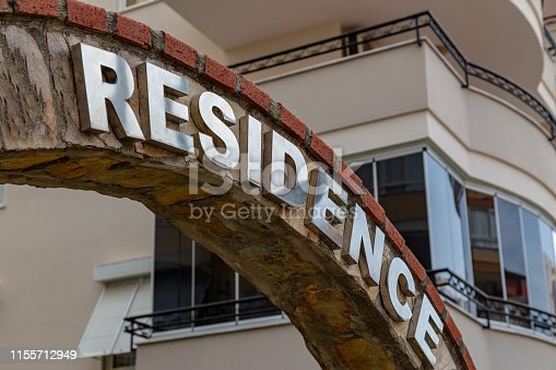 istock Shiny metal words residence on a stone arch in front of the multi stored building at a troical resort. Home investment concept. 1155712949