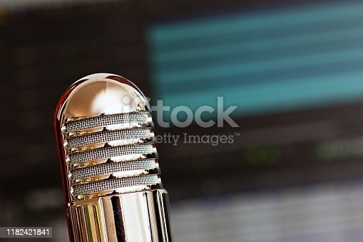 Old-fashioned-looking microphone with recording software blurred in the background.  Please note: The microphone is not the forbidden Shure SH-55. It's a cheap Chinese knockoff that imitates the general vibe but none of the specifics of the design. Thanks.