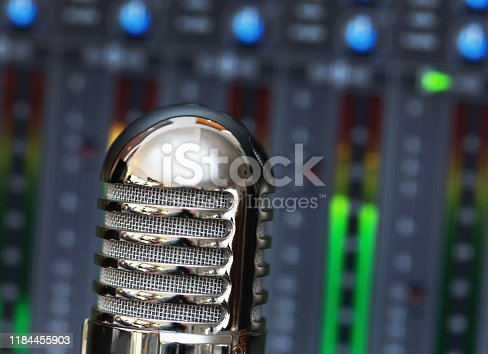 Old-fashioned-looking microphone with recording software blurred in the background.