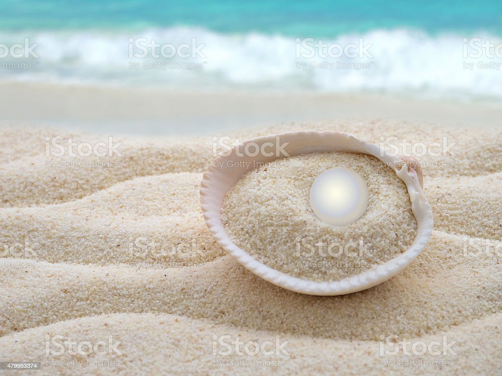 Shiny pearl in the shell on the beach stock photo