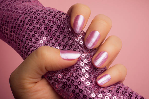 shiny pink nails The female hand with shiny pink nails is holding a pink textile with pink glitters on pink background. Manicure concept. pink nail polish stock pictures, royalty-free photos & images
