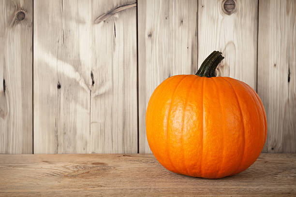 Shiny pumpkin set on a table against a wooden wall stock photo