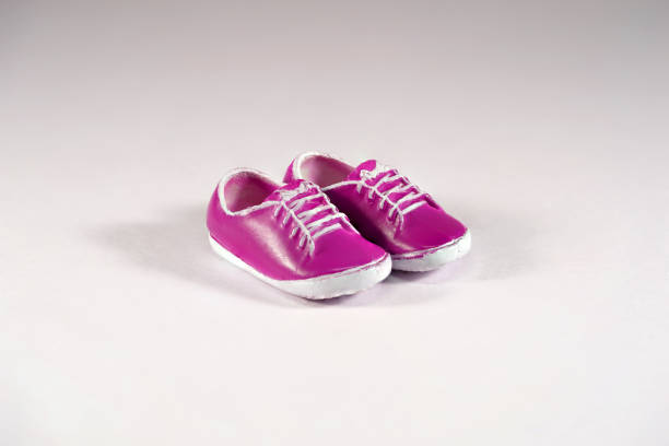 Shiny Purple Toy Shoes with laces on White Background. High Resolution stock photo