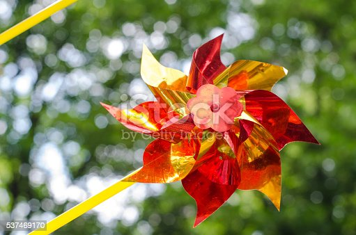 istock Shiny red and yellow pinwheel toy on summer background 537469170