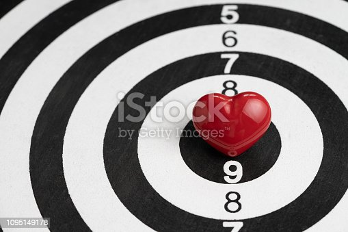 istock Shiny red heart shape on center of archery black and white circle dartboard with score numbers, love target Valentines background 1095149178