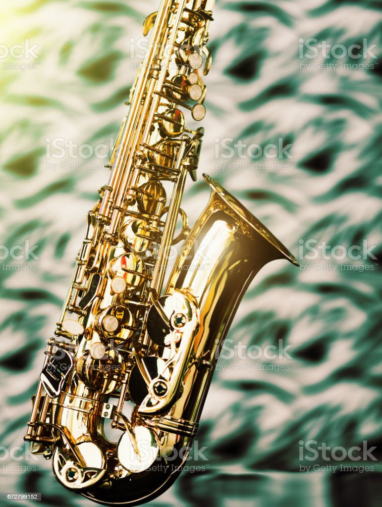 Shiny saxophone against defocused patterned background. stock photo