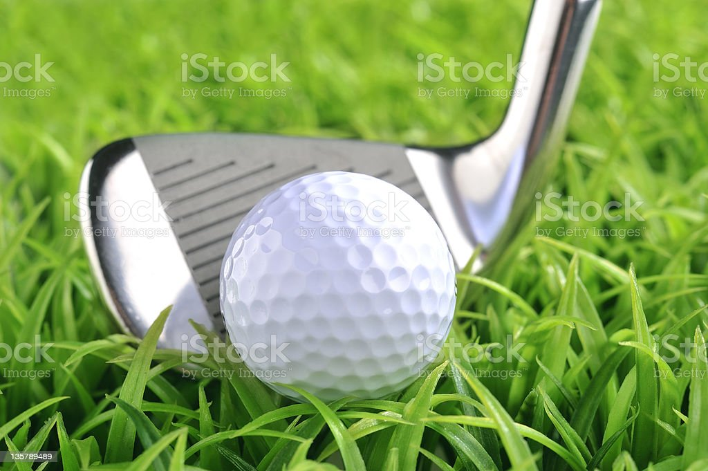 A shiny silver golf club hitting a golf ball royalty-free stock photo