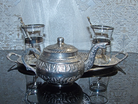 A shiny silver teapot and glasses on a tray. Cooking battery. Kitchen utensils