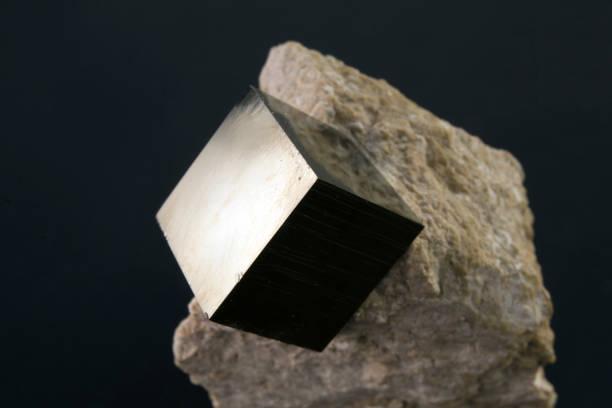 Shiny smooth regular shape pyrite cube on a dark background stock photo