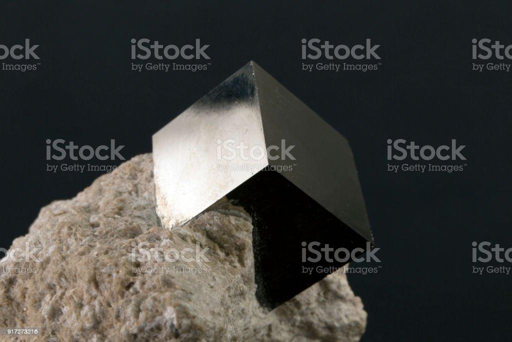 Shiny smooth regular shape pyrite cube on a dark background royalty-free stock photo