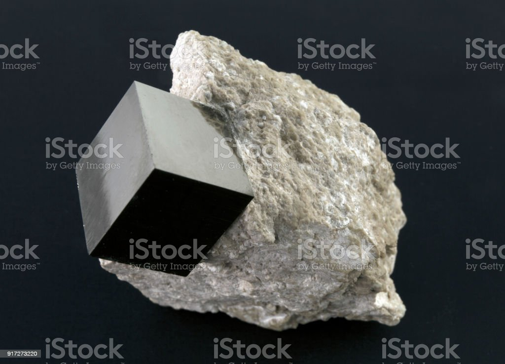 Shiny smooth regular shape pyrite cube on a dark background stock photo