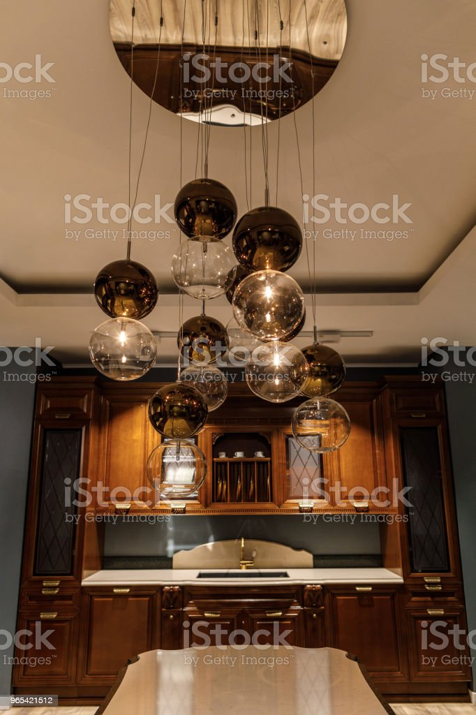 Shiny spherical chandelier over elegant wooden counter in kitchen royalty-free stock photo