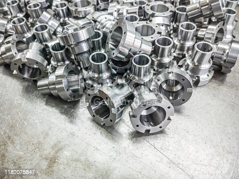 Shiny steel parts after cnc turning, drilling and machining on steel surface selective focus composition background.