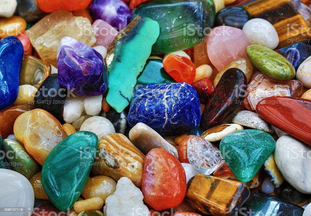 Shiny Stones A collection of polished stones including Fluorite, Amethyst, Carnelian, Tiger Eye, Lapis Lazuli, Rose Quartz, Icelandic Spar, Quartz and other stones Amethyst Stock Photo
