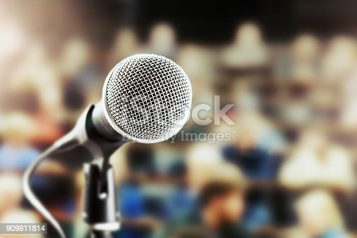istock Shiny vocal microphone with defocussed  audience in background 909911814