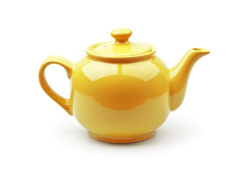 A shiny yellow teapot on a white background