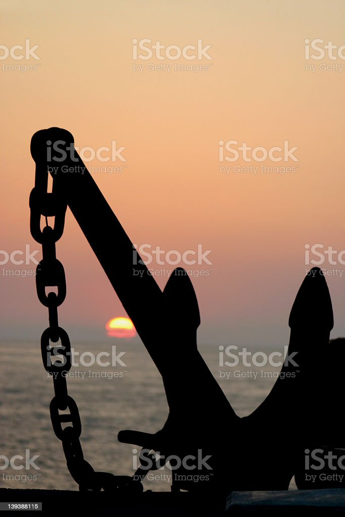 Ship anchor on the shore overlooking the ocean at sunset royalty-free stock photo