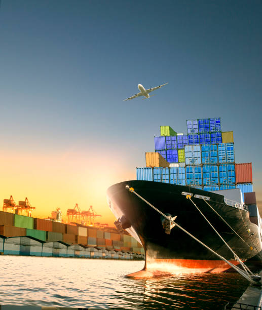 ship and container box and cargo plane flying over shipping dock use for logistic and international transportation stock photo