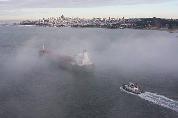 Ship and Tug Boat Pass Under the Golden Gate Bridge stock photo