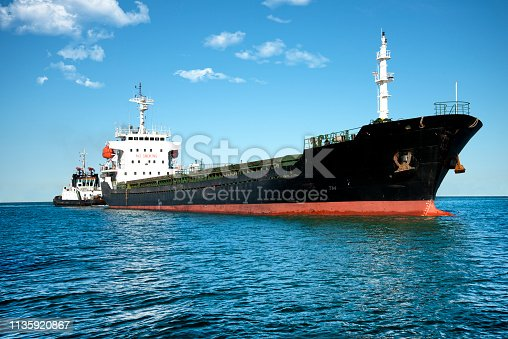 Ship and tugboat in the harbor