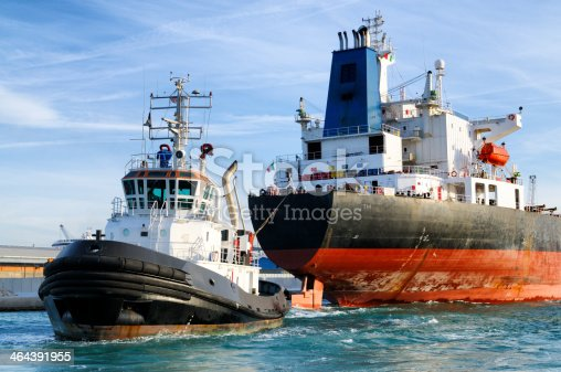 Tugboat pulling cargo ship in the harbor