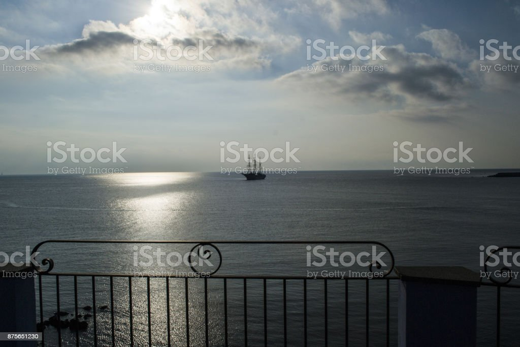 ship arriving at sunset to the coast stock photo
