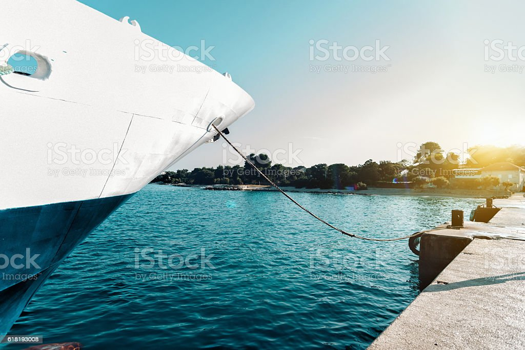 ship at landing stage at croatian coast in morning light stock photo