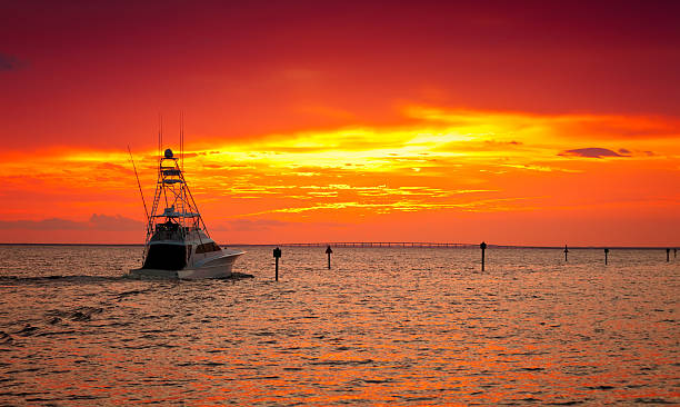 A ship at sea in the sunset with orange skies Large fishing boat going out for a sunset cruise in Destin, Florida bay of water stock pictures, royalty-free photos & images