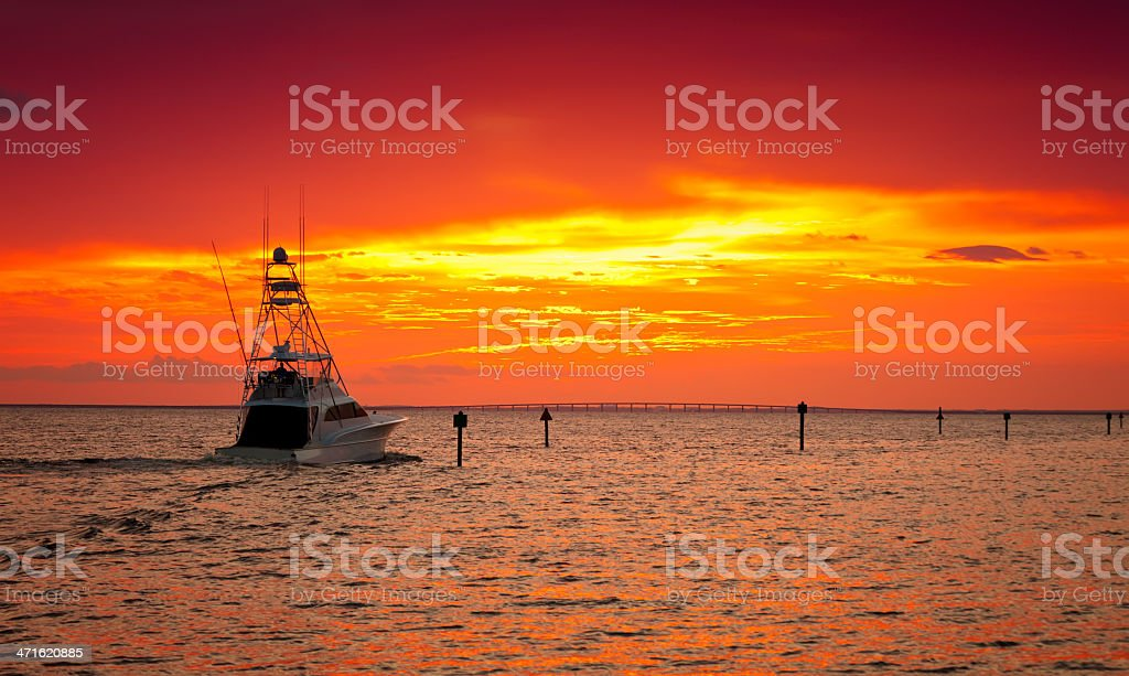 A ship at sea in the sunset with orange skies stock photo