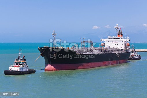 tugboats helping a tanker at navigating