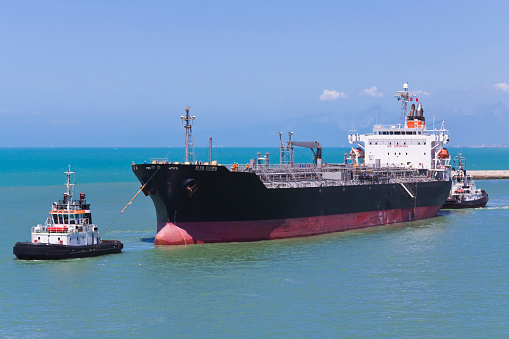 tugboats helping a tanker at navigating
