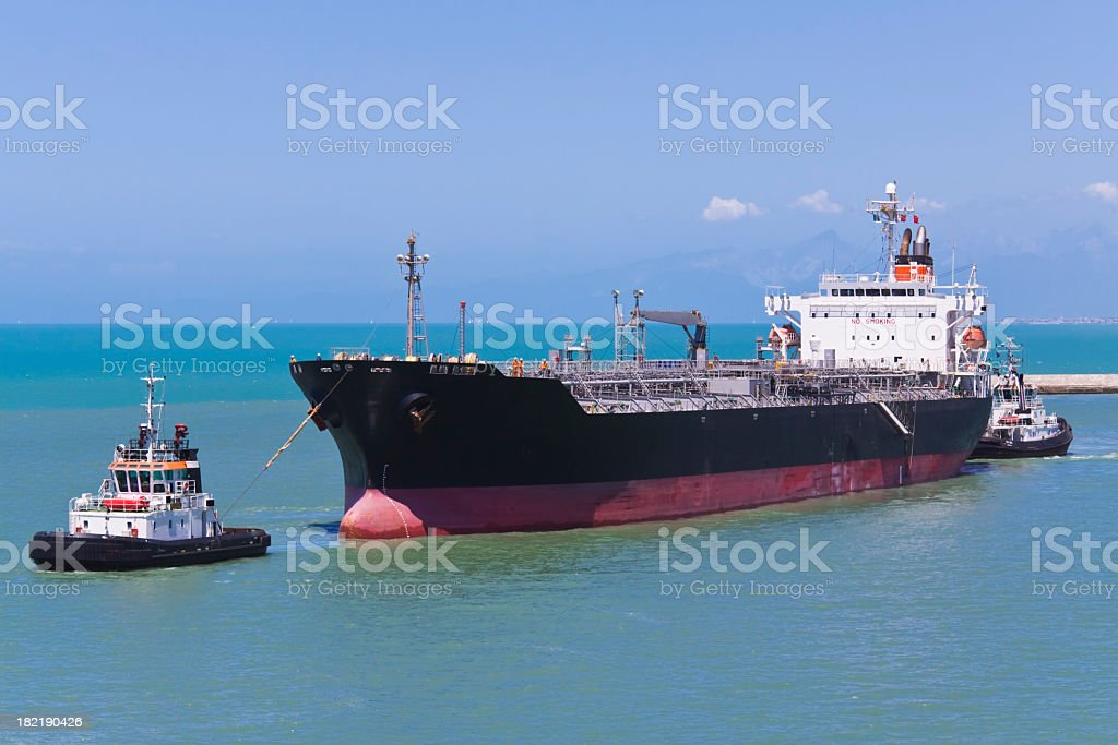 A ship being pulled by a tugboat in the water stock photo