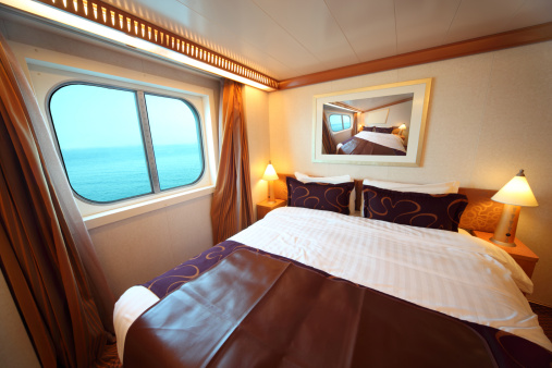 Ship cabin: bed and window with view on sea