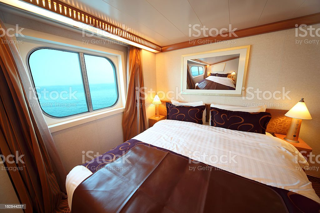 Ship cabin: bed and window with view on sea stock photo