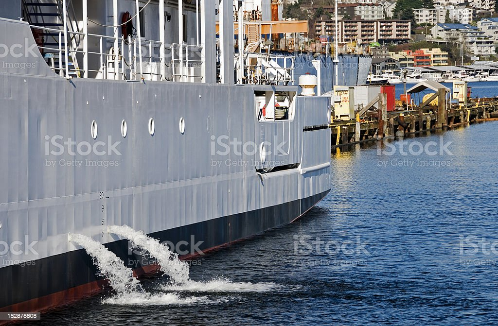 Ship discharging ballast water into lake stock photo