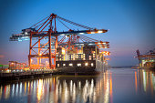 Harbour at night in Hamburg, Germany. Container terminal with container cargo ships.