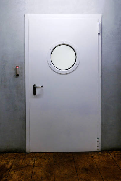 Ship door with porthole and industrial environment. stock photo