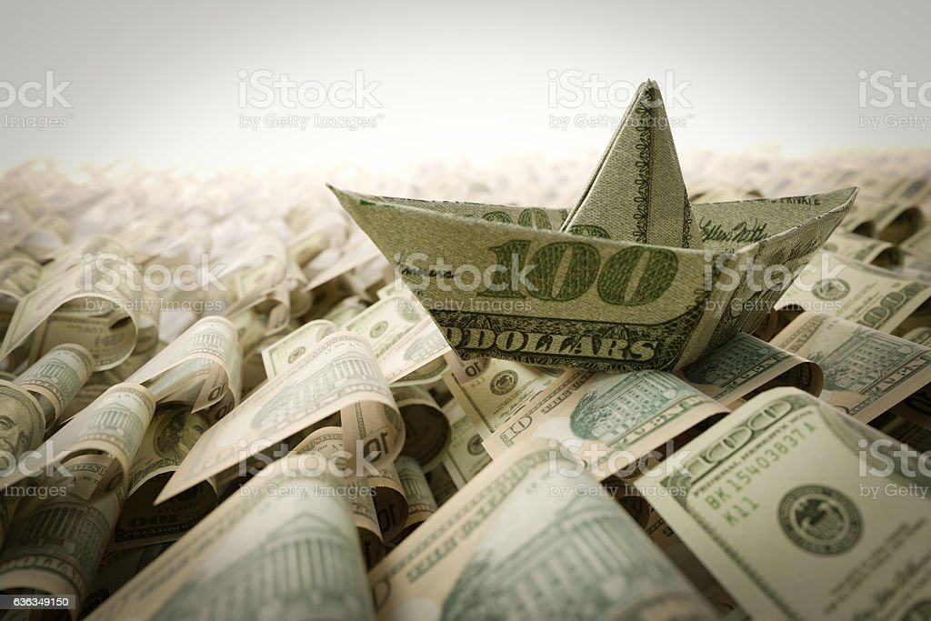Ship from dollar paper in the money sea concept stock photo