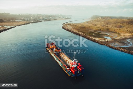 A dredge ship in a river about to end at the sea
