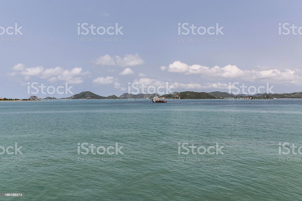 ship in the sea against blue mountains , Rayong Thailand royalty-free stock photo