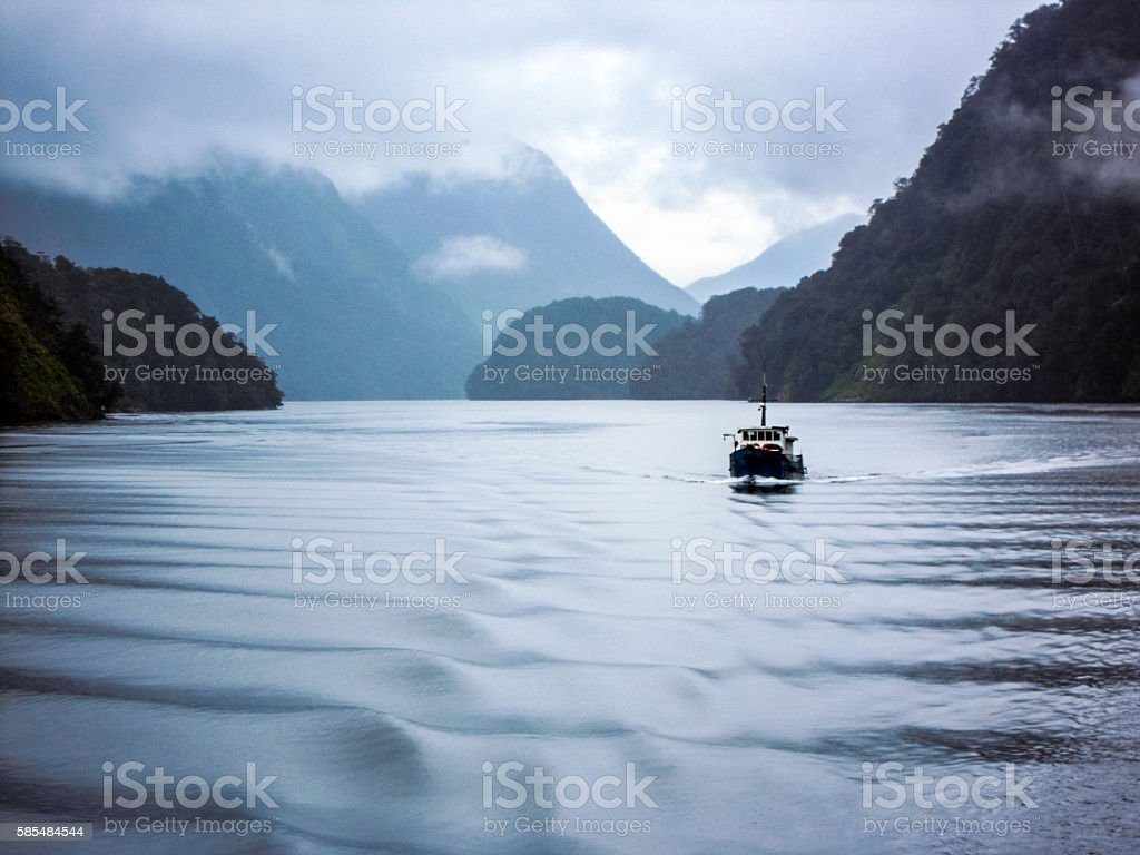 Ship is crossing the Doubtful Sound, New Zealand stock photo