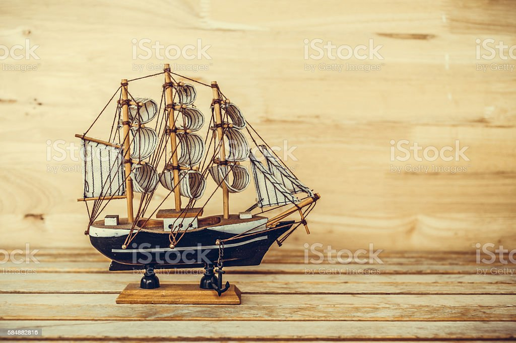 ship model on the table and wood background, vintage photo stock photo