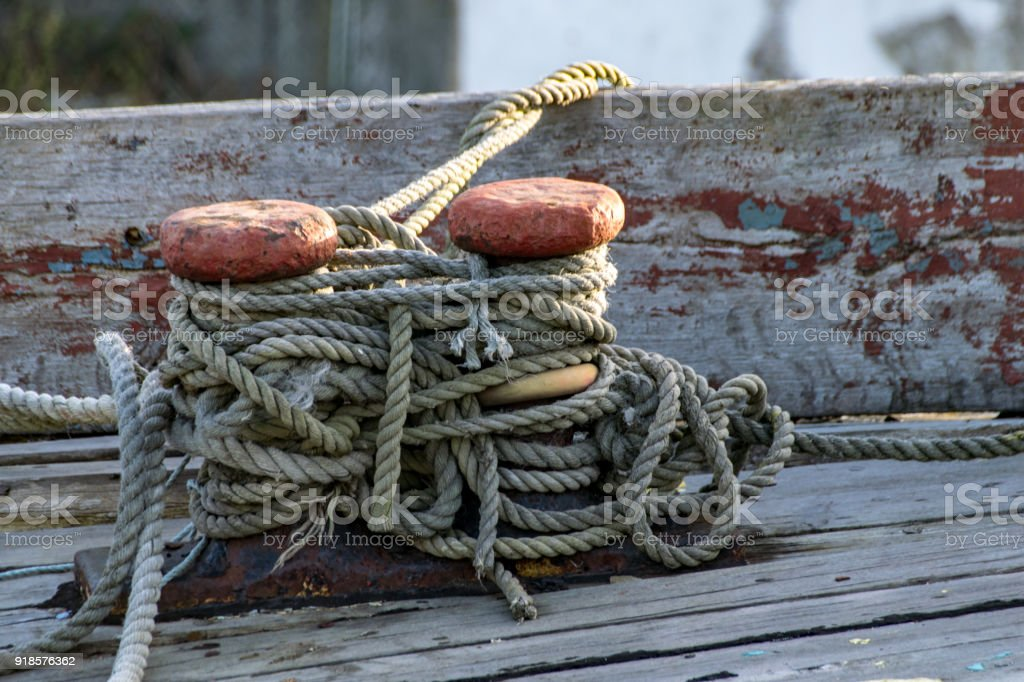 Ship Mooring Ropes Secured Around A Boat Bollard Stock Photo