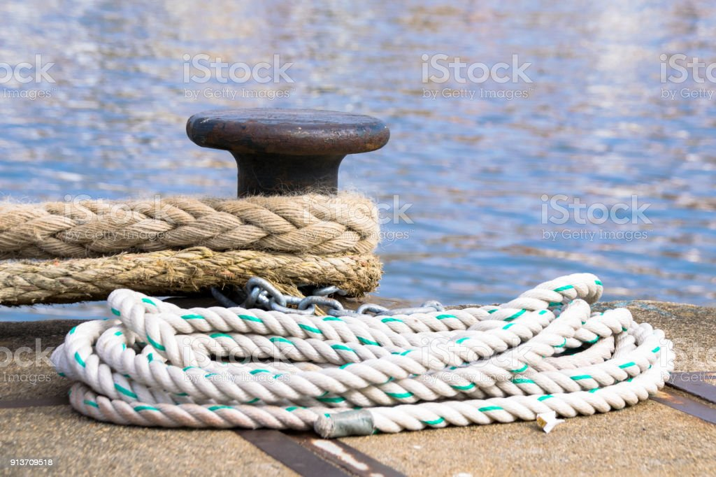 Ship Mooring Ropes Secured Around A Port Bollard Stock Photo